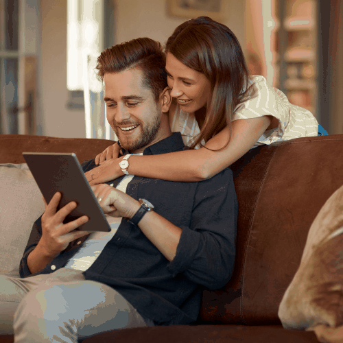 Cropped shot of a couple using a digital tablet while relaxing at home