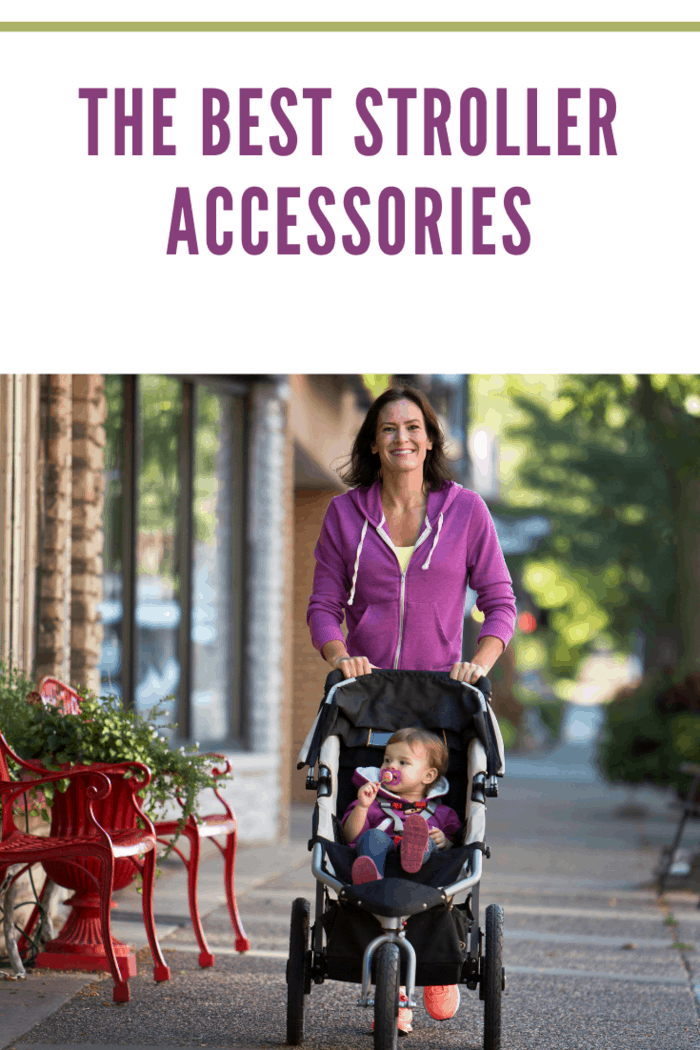 Mother pushing daughter in jogging stroller through an urban area.