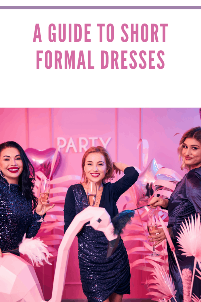 Three beautiful smartly dressed women with ostrich feathers and alcoholic drinks posing for the camera