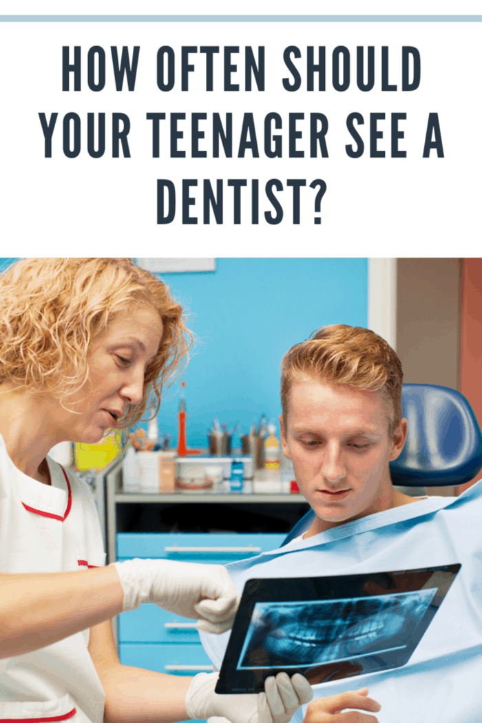 """""""Portrait of an teenager boy, man, sitting in a dentist chair at dentist office. Selective focus to teenager face, dentist explaining x-ray image to patient."""""""