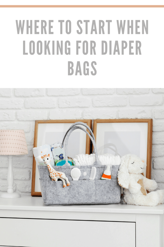 diaper bag with toy, diapers and accessories on white background