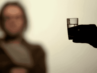 Hand holding vodka glass offering drink alcohol, addiction willpower, rehab