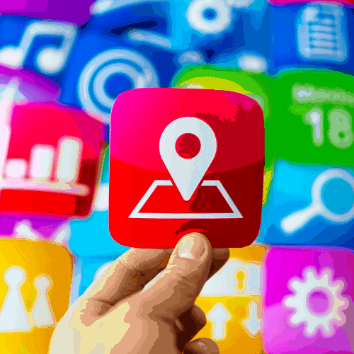 hand holding a printed on paper location icon over many other multicoloured application icons