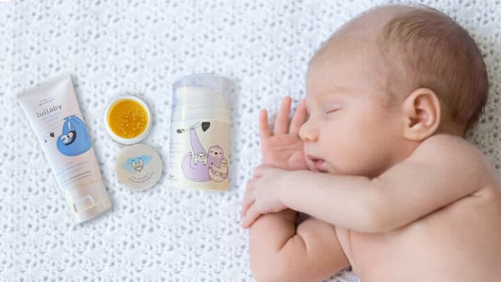 kiss kiss goodnight product line on white crochet blanket next to sleeping baby.