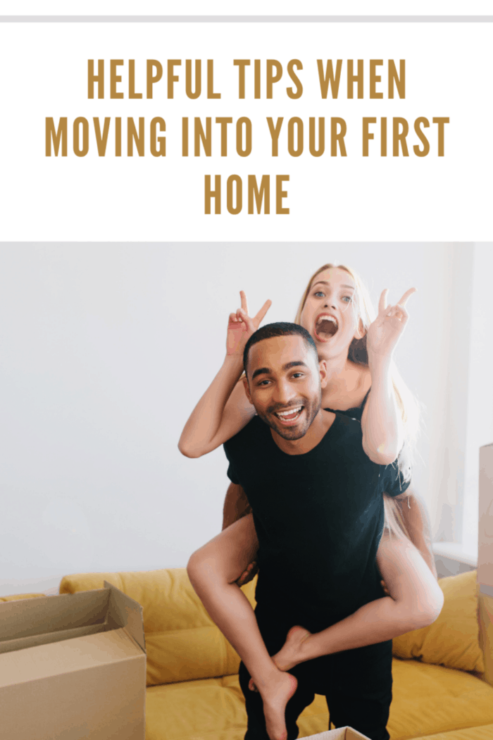 Very happy couple celebrating first day in new home, finishing packing, unpacking boxes, having fun in new apartment. Young man lifting woman on his back in room with yellow sofa.