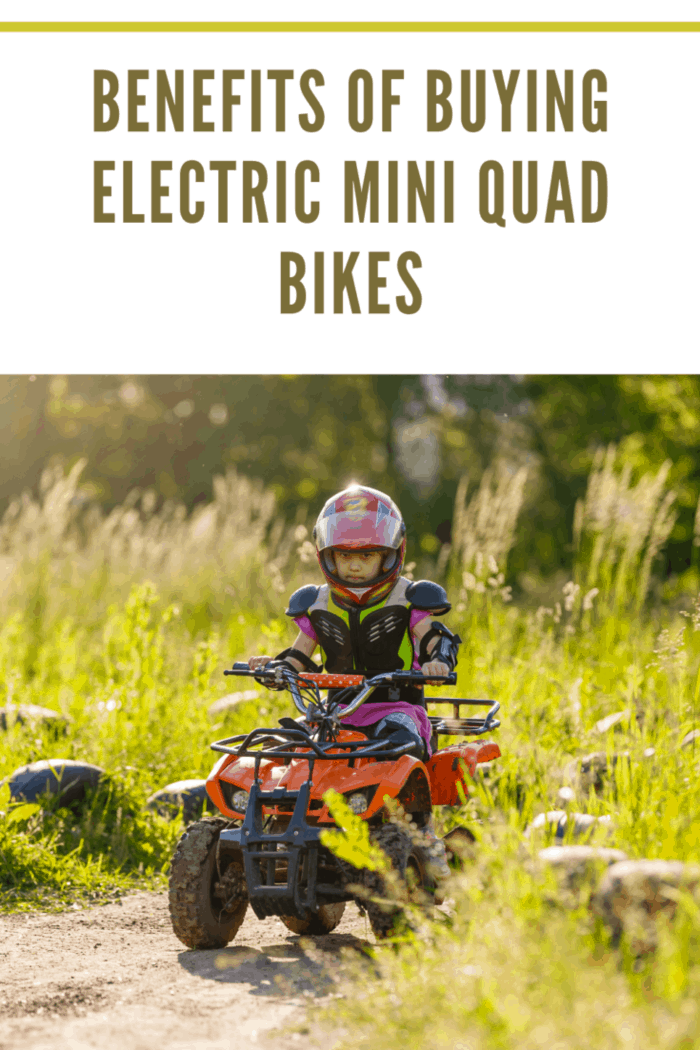 The little girl rides a quad bike. A mini quad bike is a cool girl in a helmet and protective clothing. Electric quad bike electric car for children popularizes green technology