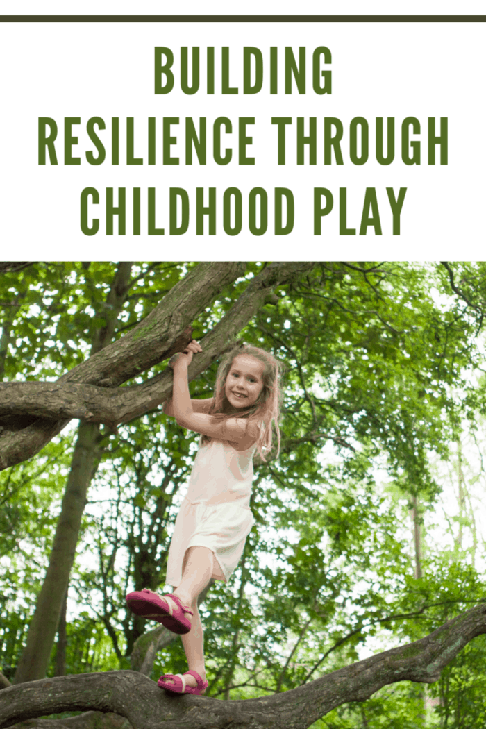 A happy little girl is climbing a tree in a wooded area
