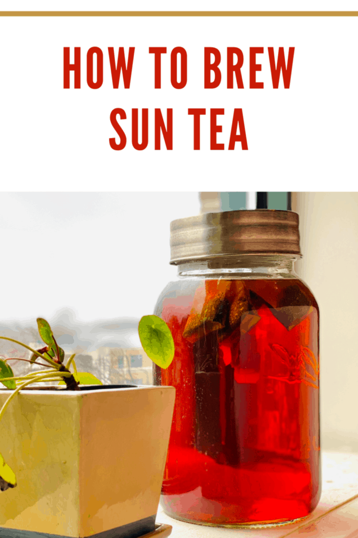 A jar of homemade sun tea sits on a weathered wooden deck with sunshine highlighting it