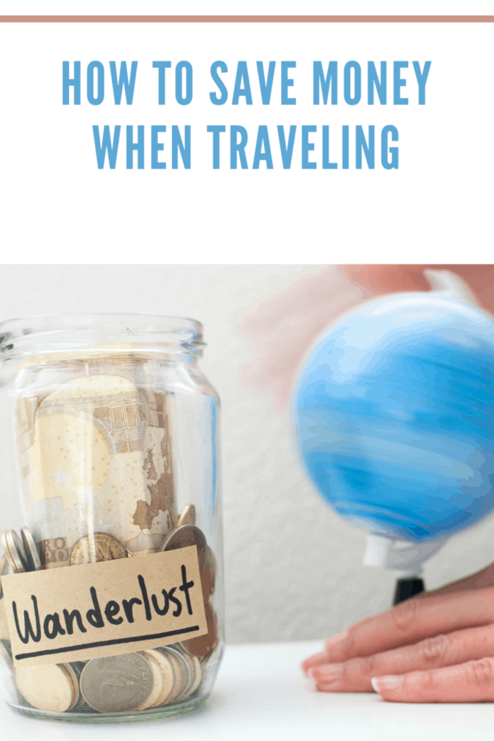 Saving up money to travel concept / Money jar with wanderlust note and rolling world map globe.