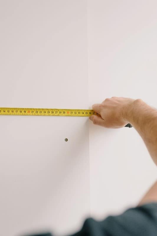 taking measurements of wall