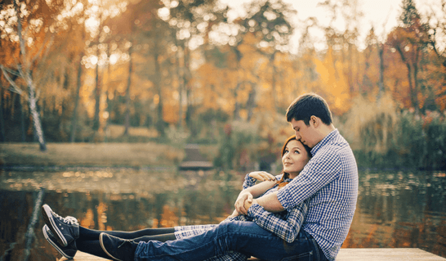 man and woman who worked hard at finding the perfect partner on dock in fall wrapped in each other's arms.