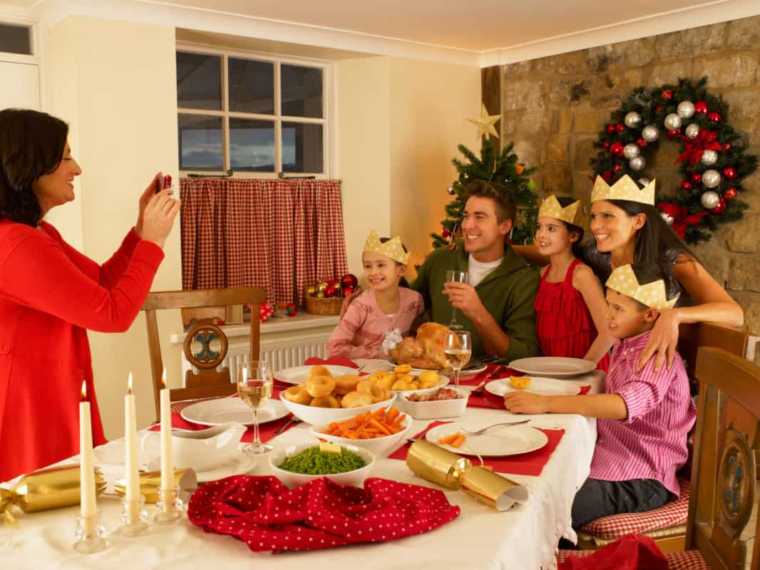 Family taking photos at christmas dinner