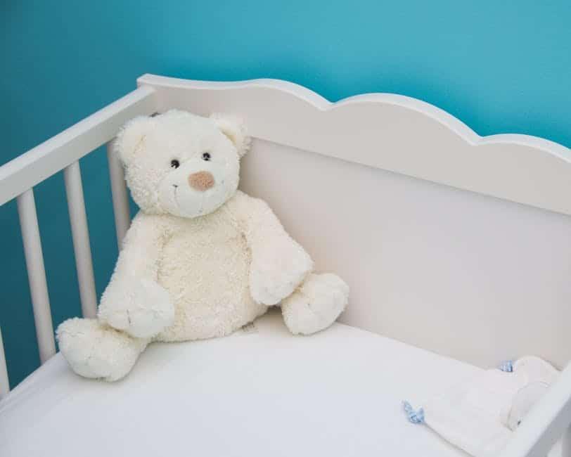 white crib with white teddy bear