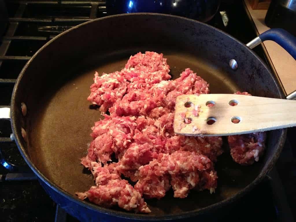 raw sausage in frying pan